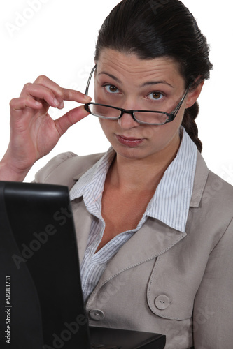 Serious businesswoman watching over her glasses