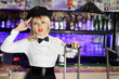 Glamorous blonde girl in black peaked cap sits near bar counter.