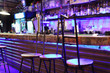 Unusual metal bar stools stand near bar counter in blue light.