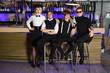 Four glamorous rock band pose near bar counter