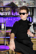Glamorous young man in sunglasses sits near bar counter