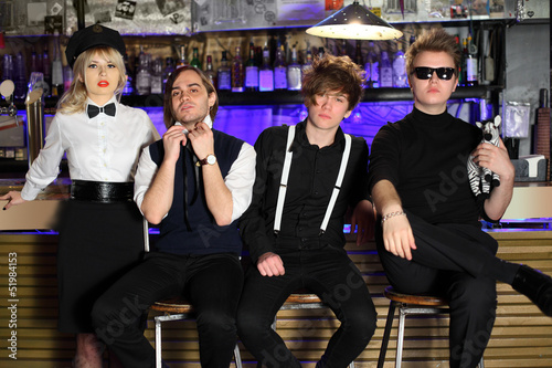 Four popular rock band in black and white pose near bar counter.