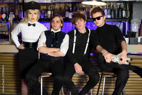 Four young rock band in black and white pose near bar counter.