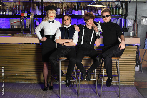 Four glamorous rock band pose near bar counter