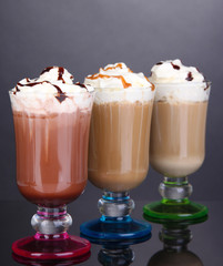 Layered coffee in glass on table on grey background