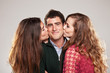 two young women kissing handsome man standing between them