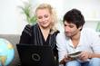 a couple doing internet near a globe