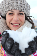 woman all smiles at ski resort with snow in hands