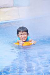 Boy learn to swim at hotel pool
