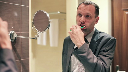 Young businessman brushing teeth with a toothbrush in bathroom
