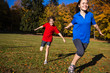 Girl and boy running, jumping in park - focus on boy