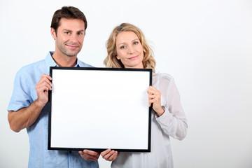 Couple holding frame