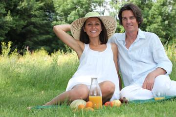 Couple sat in field