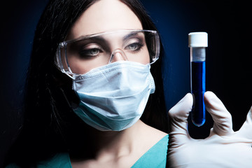 scientist looking at tube with blue liquid in dark