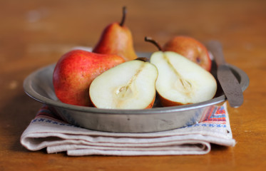 Fresh ripe pears in a plate with napkin and knife