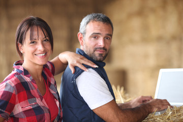 Farmer couple with laptop in barn