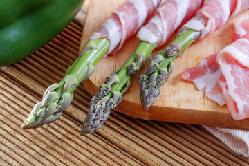 Bacon and asparagus on a wooden background