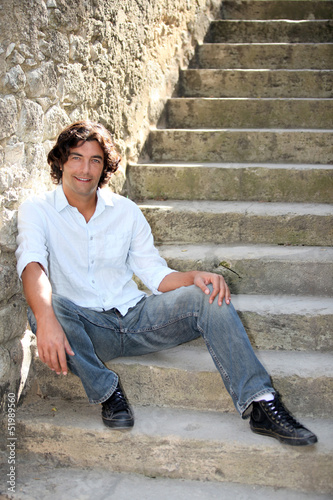 35 years old man sitting on downstairs