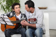 father and teenage son playing the guitar