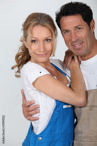 Couple wearing work overalls