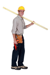young carpenter in studio carrying plank over his shoulder