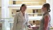 Two businesswomen chatting in office building, steadicam shot