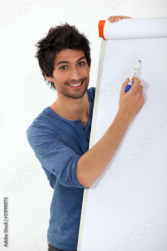 young man writing with marker on a white board