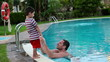 Happy father in swimming pool talking to his son
