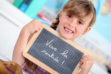 Little girl writing on chalkboard