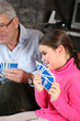 little girl playing cards with grandfather