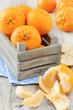 Delicious mandarins oranges in a crate on wooden surface