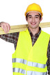 portrait of young joiner carrying planks over shoulder