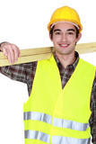 portrait of young joiner carrying planks over shoulder poster