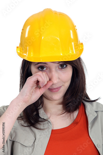 cute young female apprentice wiping tears