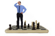Stressed businessman standing on giant chess board