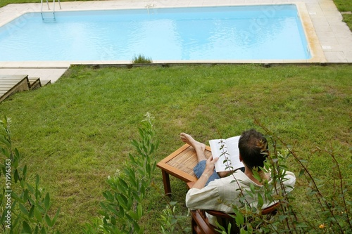 Woman reading book poolside