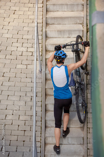 Professional cyclist coming up the steps with bicycle