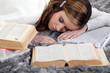 female student sleeping amid books