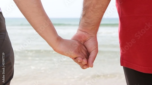 A young couple on the beach holding hands