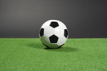 Balón de fútbol y césped artificial, fondo negro