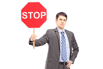 A businessman holding a stop sign