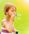 Baby girl blowing soap bubbles
