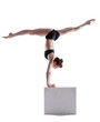 Flexible gymnast balancing on cube in studio