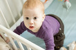 Top view of adorable baby boy trying to stand up in his cot