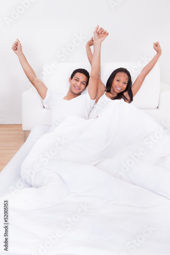 Couple Raising Hands On Bed