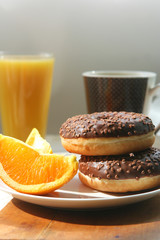 Donuts, oranges and juice for breakfast