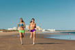 Sport and Fitness - people jogging on beach