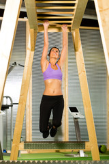 Woman hanging at high or horizontal bar