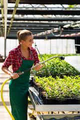 Female commercial gardener watering plants