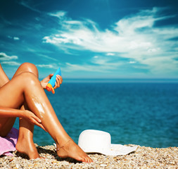 Tan Woman Applying Sunscreen on Legs